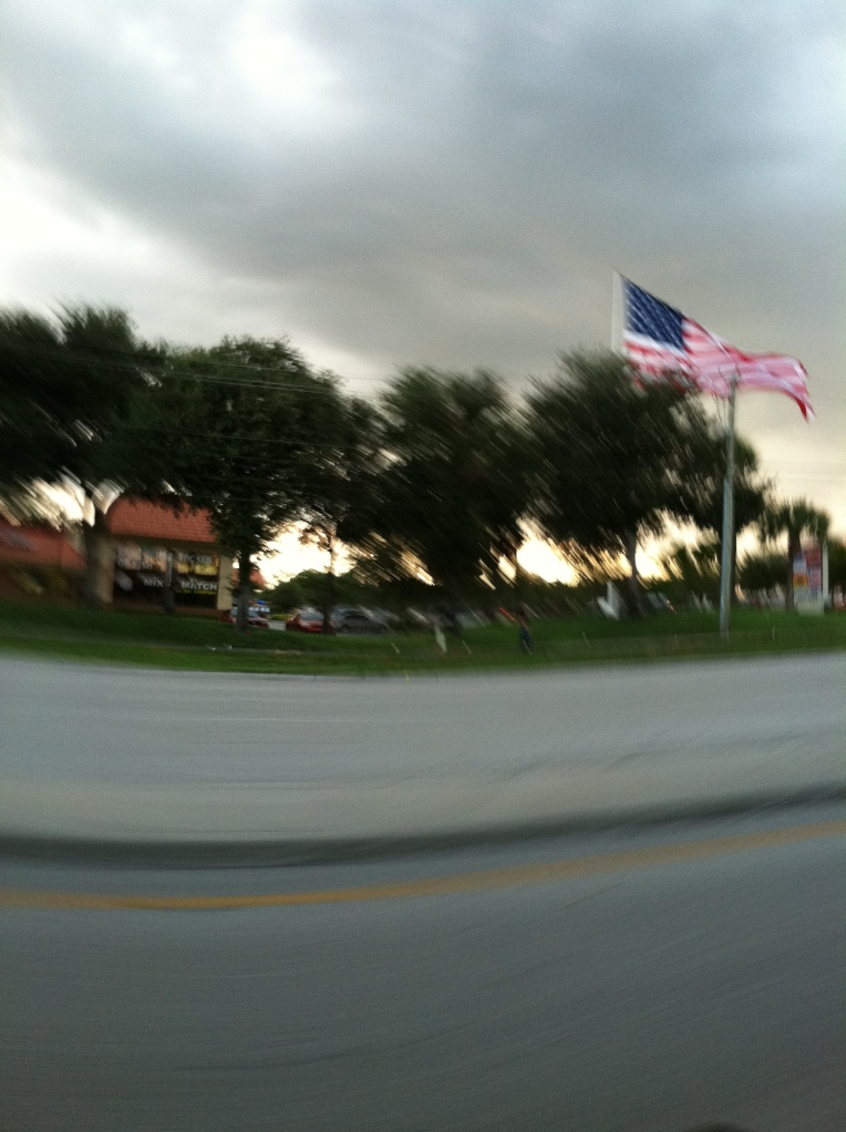 Very large American Flag waving in the breeze on a cloudy evening