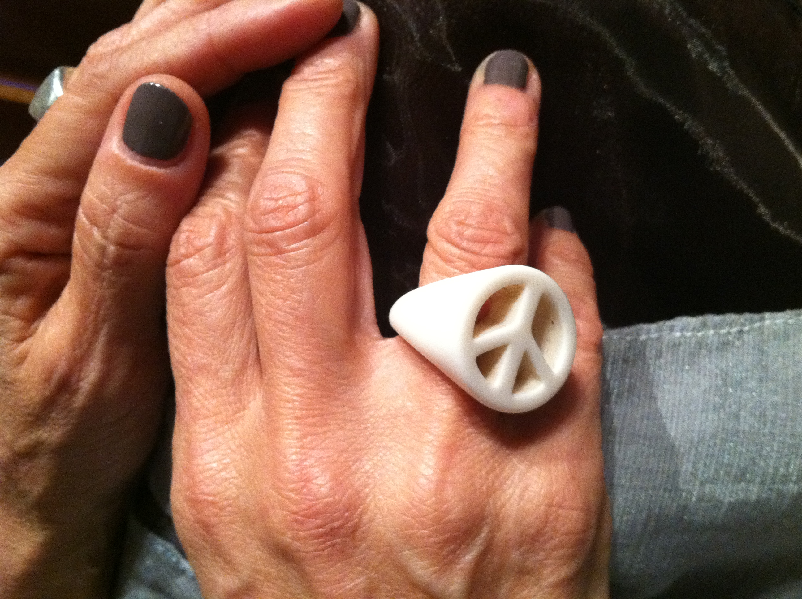 Jill's hands in lap wearing dark nail polish wearing her white peace sign ring