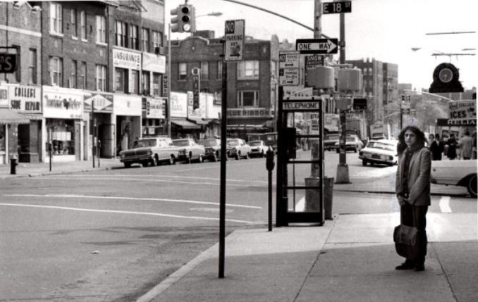 Jill Slaughter as teenager on street corner, standing in front of telephone booth in Brooklyn near train station