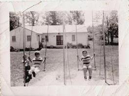 Jill Slaughter and older sister Susan swinging on swings