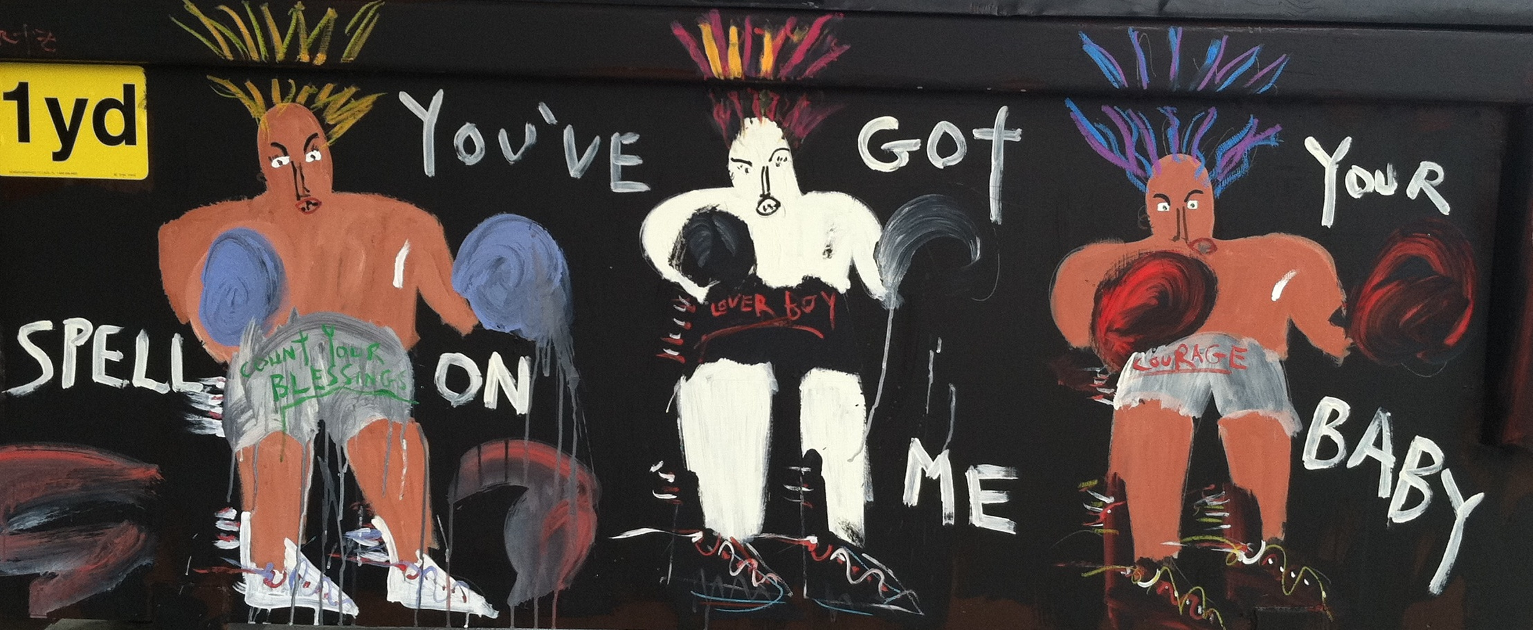 "Three boxers painted on a dumpster with ""You've Got Your Spell On Me Baby"" painted across the image"